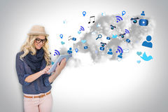 Stylish blonde using tablet pc with app icons and cloud Stock Photography