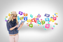 Stylish blonde using tablet pc with app icons Royalty Free Stock Photos