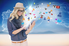 Stylish blonde using tablet pc with app icons Royalty Free Stock Images