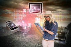 Stylish blonde using tablet pc with connecting devices Stock Photo