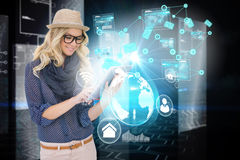 Stylish blonde using tablet pc with interfaces and email icons Royalty Free Stock Photo
