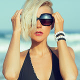 Stylish blonde walking on the beach in fashion accessories Stock Photos