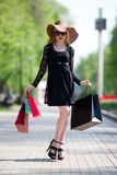Stylish blonde woman in black dress, sunglasses and hat with shopping bags walking in the city. Holiday concert Royalty Free Stock Photo