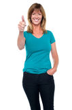 Stylish blonde woman gesturing thumbs up. Fashionable middle aged blonde showing thumbs up sign to the camera Stock Photo