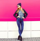 Stylish blonde woman model in full-length posing wearing rock black style jacket, hat on city street over colorful pink wall royalty free stock images