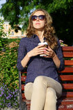 Stylish blonde woman in sunglasses with disposable coffee cup sitting on bench Stock Image