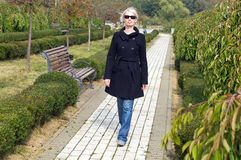 Stylish blonde woman walking in  in park Stock Photo