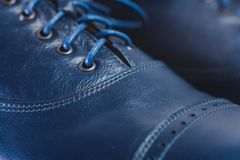 Stylish black mens crafted shoes for ballroom dancing. Stylish blue mens crafted shoes with laces from skin and suede. macro photography of crafted mens blue Stock Photos