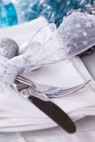 Stylish blue and silver Christmas table setting. With a pretty translucent bow on white dinnerware with silver cutlery, pine cones and baubles, high angle close Royalty Free Stock Photo