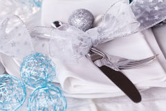 Stylish blue and silver Christmas table setting. With a pretty translucent bow on white dinnerware with silver cutlery, pine cones and baubles, high angle close Stock Image