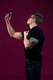 Stylish bodybuilder doing selfie with smartphone Stock Photos