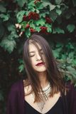 Stylish bohemian girl with modern jewelry posing under green branches of guelder rose in street. Hipster girl calm portrait among. Leaves and berries. Eco model royalty free stock images