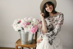 Stylish boho girl in hat sitting at metal bucket with peonies on rustic wooden chair.Beautiful hipster woman smiling at big. Peonies bouquet. Countryside living royalty free stock photography