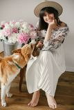 Stylish boho girl playing and smiling with cute golden dog at metal bucket with peonies on rustic wooden chair in home. Beautiful stock photo