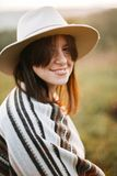 Stylish boho girl smiling  in sunny light at atmospheric sunset in meadow. Happy hipster woman in poncho and hat enjoying stock images