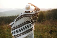 Stylish boho girl walking in sunny light at atmospheric sunset in meadow. Happy hipster woman in poncho and hat enjoying traveling stock images