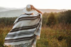 Stylish boho girl walking in sunny light at atmospheric sunset in meadow. Happy hipster woman in poncho and hat enjoying traveling royalty free stock images