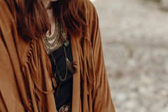 Stylish boho woman look. gypsy hipster girl in fringe jacket wit. H feather bronze accessory. wanderlust summer travel. atmospheric moment. space for text royalty free stock photos