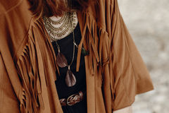 Stylish boho woman look. gypsy hipster girl in fringe jacket wit. H feather bronze accessory. wanderlust summer travel. atmospheric moment. space for text stock photo