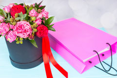 Stylish bouquet of pink and red roses and red ribbon in a circul. Ar black box near pink gift bag. Valentines and anniversary concept Royalty Free Stock Image