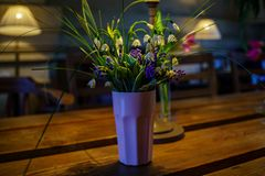 Stylish bouquet of snowdrops and bluebells in a ceramic vase glass in the designer interior of the cafe. Conceptual art design photography stock image