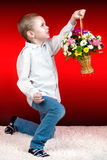 Stylish boy, a beautiful child brings a basket of beautiful, spring,fragrant,flowers. Beautiful boy with flowers for mom.Stylish boy stock images