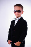 Stylish boy. In a black suit with a butterfly and in glasses Stock Images