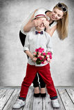 Stylish boy with a bouquet of roses waiting for his mom to surprise her.Spring concept of family vacation. Women`s day,mother`s da Royalty Free Stock Images