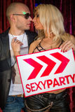 Stylish boy and girl kiss with a sign. In the girls hand stock photos