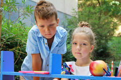Stylish boy and girl playing school outside. Education and kids fashion concept Stock Photos