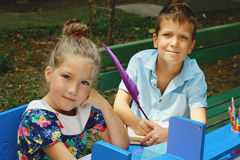 Stylish boy and girl playng school outside. Education and kids fashion concept Royalty Free Stock Images