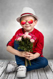 Stylish boy in a hat holding a bouquet of roses.Children`s fashion. Stylish boy in a hat holding a bouquet of roses stock photo