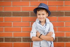 Stylish boy in Hat posing on a brick wall Stock Image