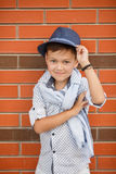 Stylish boy in Hat posing on a brick wall Stock Photos
