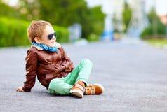 Stylish boy in leather jacket posing on the ground Royalty Free Stock Image
