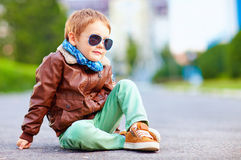 Stylish boy in leather jacket sitting on the road Royalty Free Stock Image