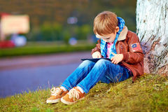 Stylish boy playing on tablet, at the city park Royalty Free Stock Image