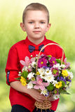 Stylish boy,pretty boy with a basket of flowers. Stylish boy gives the flower basket Royalty Free Stock Image