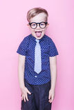 Stylish boy in shirt and glasses with big smile. School. Preschool. Fashion. Studio portrait over pink background Royalty Free Stock Photos