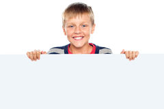 Stylish boy standing behind big blank banner ad Royalty Free Stock Photography