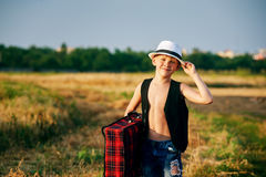Stylish boy with suitcase on rural road Stock Photo