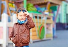 Stylish boy takes off sunglasses, on city street Stock Photos