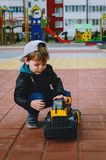 Stylish boy of three years old in a black trend jacket and a cap baseball cap plays in the yard with a big yellow car excavator. Stylish guy, children`s royalty free stock photos