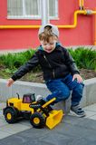 Stylish boy of three years old in a black trend jacket and a cap baseball cap plays in the yard with a big yellow car excavator. Stylish guy, children`s stock image