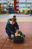 Stylish boy of three years old in a black trend jacket and a cap baseball cap plays in the yard with a big yellow car excavator. Stylish guy, children`s stock images
