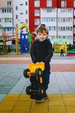 Stylish boy of three years old in a black trend jacket and a cap baseball cap plays in the yard with a big yellow car excavator. Stylish guy, children`s stock photography