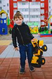 Stylish boy of three years old in a black trend jacket and a cap baseball cap plays in the yard with a big yellow car excavator. Stylish guy, children`s royalty free stock images