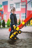 Stylish boy of three years old in a black trend jacket and a cap baseball cap plays in the yard with a big yellow car excavator. Stylish guy, children`s royalty free stock photo