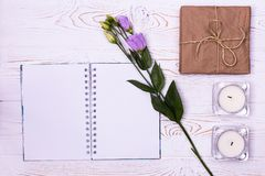 Stylish branding mockup to display your artworks.Blank notebook, Gift box wrapped in kraft paper, flower, candles on a white backg royalty free stock photos