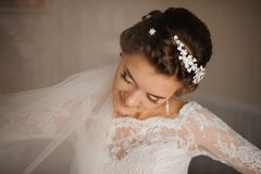Bride in a white dress and veil is standing with her head bowed. Stylish bride brunette in a white lace dress, a white veil, a hairdo with flowers and a gentle Stock Photography